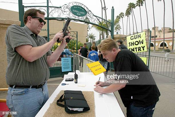 A man checks a handgun at the reception desk of the Cross Roads of the West Gun Show in Del Mar California 20 October where loade guns are not...
