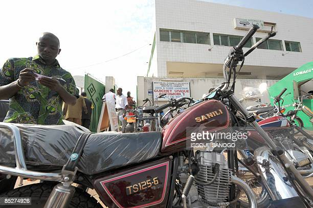 A man checks a motocycle registration in front of a revenue and customs services center in Bouake on March 3 2009 Prime Minister Guillaume Soro...