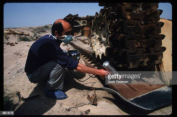 A man checks an abandoned Iraqi tank for radiation levels May 1 1998 in Basra Iraq Able to destroy armored vehicles the silver bullet was used...