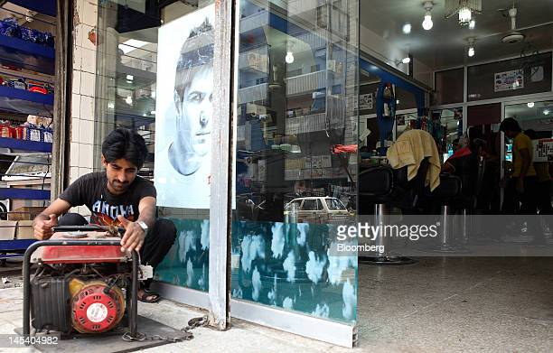 A man checks an electric generator outside his shop during a power outage in Karachi Pakistan on Monday May 21 2012 Karachi's 18 million people face...