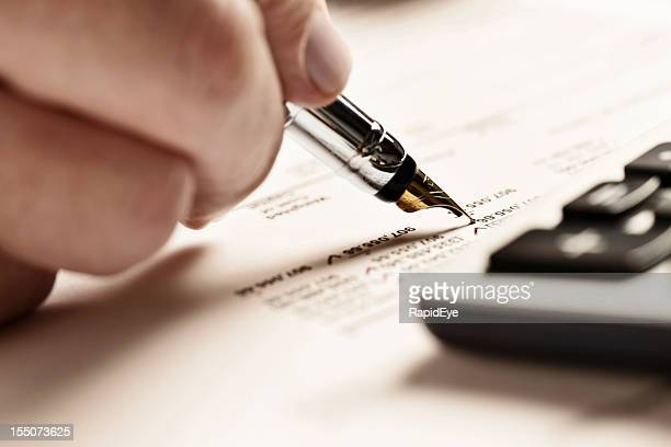 Man checks document carefully with fountain pen, calculator standing by