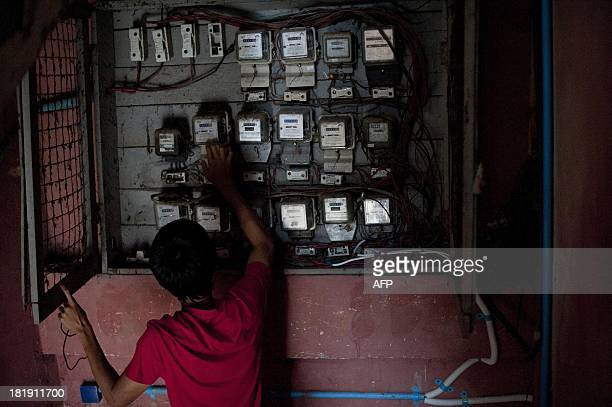 A man checks electricity meters at a building in downtown Yangon on September 26 2013 The World Bank approved on September 24 aid for a power plant...