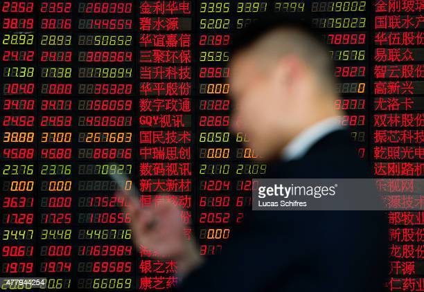 A man checks his cell phone in front of a Stock Exchange board in Shenyin and Wanguo Securities' brokerage house on May 12 in Shanghai China In China...