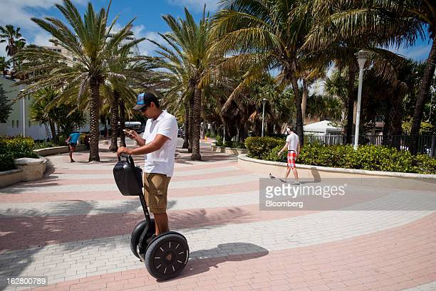 A man checks his cell phone while riding a Segway along the boardwalk in Miami Beach Florida US on Wednesday Feb 20 2013 US exports in the travel and...