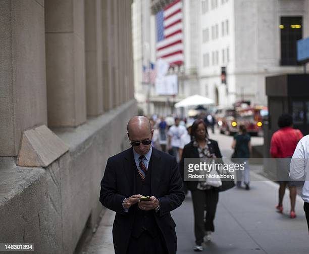 A man checks his email one block from Wall Street next to Federal Hall left June 7 2012 near the New York Stock Exchange in New York City