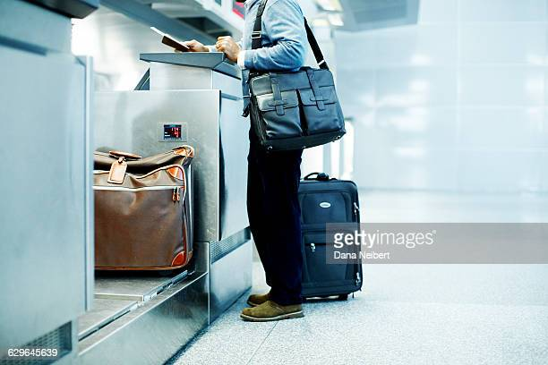 a man checks his luggage at the airport counter - shoulder bag stock pictures, royalty-free photos & images