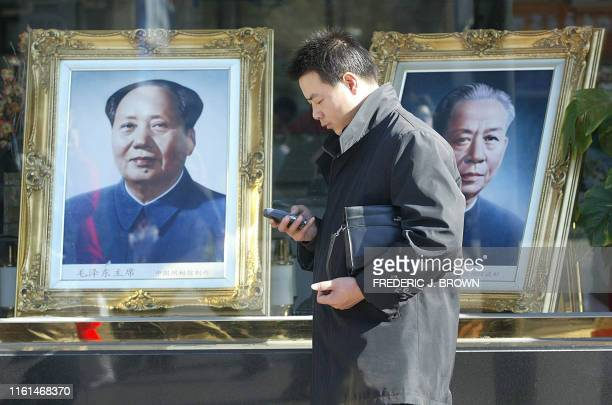 A man checks his mobile phone in front of portraits of China's lateleader Mao Zedong and former president Liu Shaoqi 07 November 2002 on display in a...