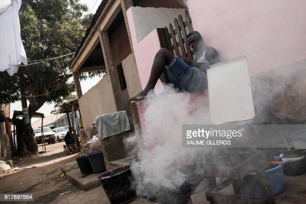 A man checks his mobile phone next to a charcoal grill in the Mindara neighbourhood in Bissau on Mardi Gras on February 13 2018 / AFP PHOTO / Xaume...