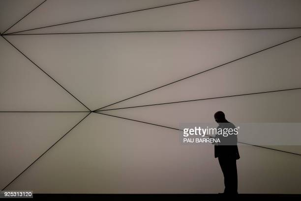 A man checks his mobilephone at the Mobile World Congress the world's biggest mobile fair on February 28 2018 in Barcelona The Mobile World Congress...