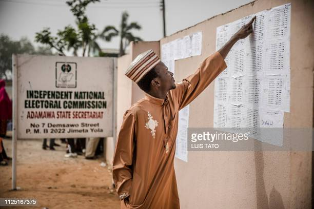 A man checks his name in voting lists at the State INEC Independent Electoral Comission Office in Jimeta on February 16 2019 Nigeria's electoral...