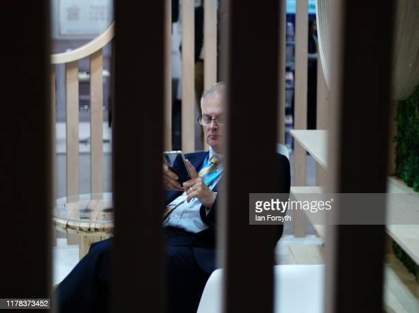 A man checks his phone as he sits in an exhibitors stand on the third day of the Conservative Party Conference at Manchester Central at Manchester...