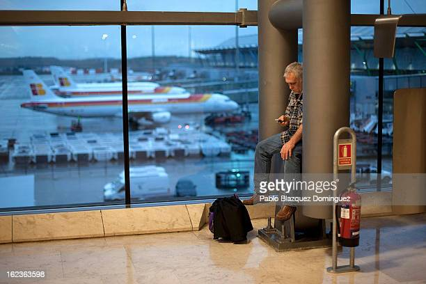 A man checks his phone at Barajas Airport while a fleet of Iberia planes are seen parked on February 22 2013 in Madrid Spain Today is the last of a...