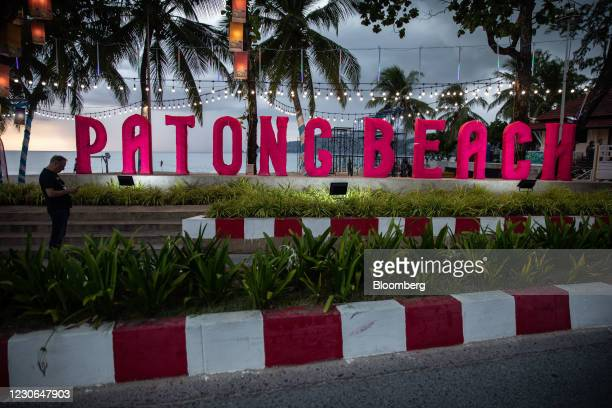 Man checks his phone near Patong Beach in Patong, Phuket, Thailand, on Saturday, Dec. 19, 2020. The tepid response to Thailands highly publicized...