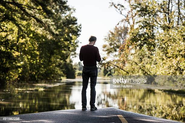 A man checks his phone on South Beltline Road October 6 2015 in Columbia South Carolina The state of South Carolina experienced record rainfall...