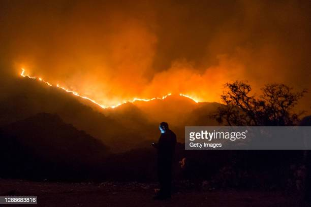 Man checks his phone will observing wildfires from La Falda on August 25, 2020 in Cordoba, Argentina. Wildfires are raging Argentina's Cordoba...