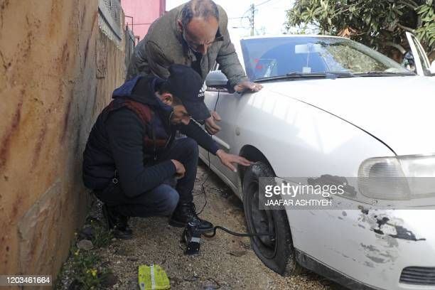 A man checks his slashed tyre in the occupied West Bank village of Yasuf near Nablus on February 26 2020 Israeli police said they were investigating...