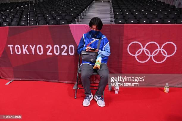 Man checks his smartphone as he sits with empty seats in background before the women's preliminary round group A handball match between Angola and...