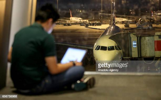 A man checks his tablet computer at the departures lounge as an airliner is seen parked at the apron in the background at Ataturk International...