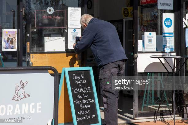 Man checks in using a QR code at a cafe offering take-away food and beverages on September 08, 2021 in Nyngan, Australia. New freedoms have been...