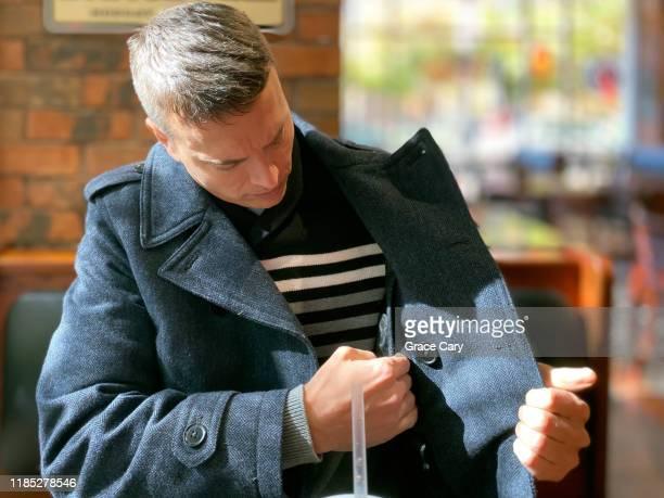 man checks interior coat pocket - jacket stock pictures, royalty-free photos & images