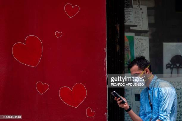 A man checks on his cel phone while lining up outside a grocery store keeping the prescribed social distance in Old San Juan Puerto Rico on April 7...