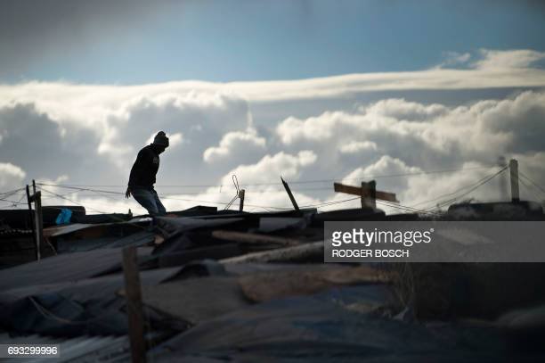 A man checks on the roofs of shacks in an informal settlement in Langa during one of the most intense storms that has hit the Western Cape Province...