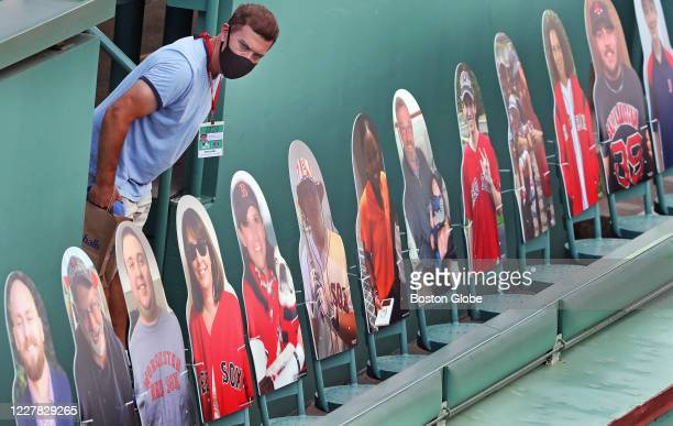 A man checks out the scene on the Green Monster where the cardboard cutout fans are placed in seats during batting practice The Boston Red Sox host...