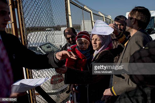 A man checks paperwork as refugees wanting to leave Turkey wait in line to pass through the border gate as a small number of Syrian refugees were...