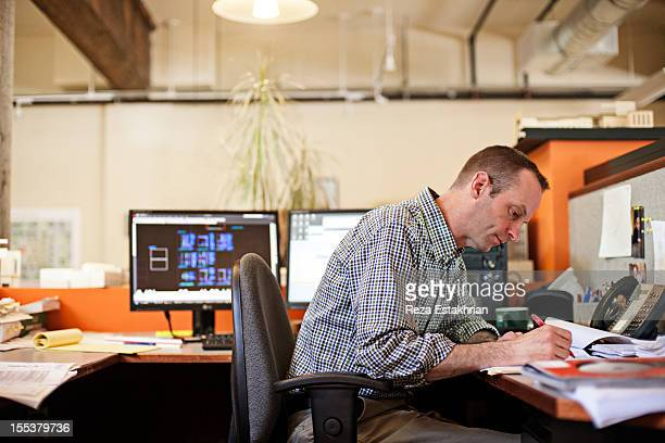 Man checks paperwork at desk