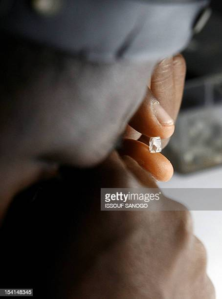 A man checks raw diamonds 10 August 2007 at the Gold and Diamond department of the Central Bank in Freetown The first Sierra Leonean diamond was...