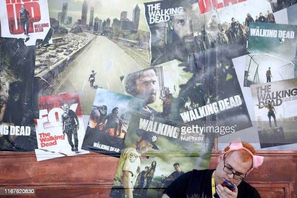 A man checks the cellphone in front of The Walking Dead posters during the Comic Con Portugal 2019 on the Day 1 in Lisbon Portugal on September 12...