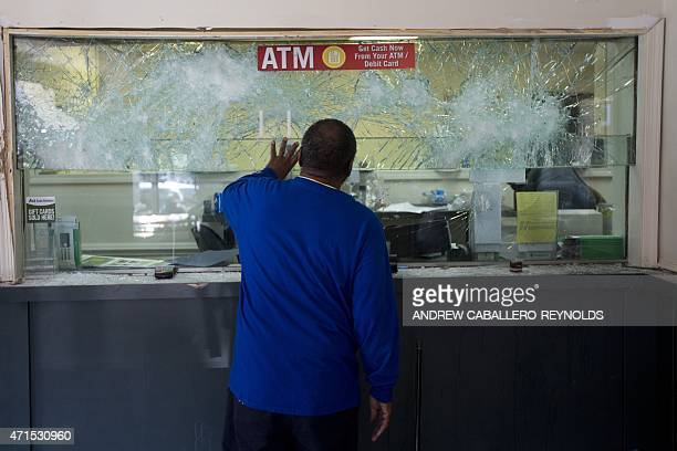 Man checks the destroyed window of a check cashing bureau at the Western District in Baltimore, Maryland on April 29, 2015. Riot police in the US...
