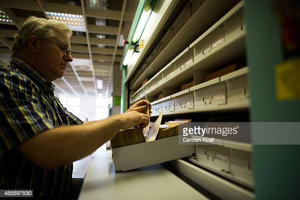 A man checks the documents at the archives of the former East German secret police known as the Stasi on September 17 2014 in Berlin Germany The...