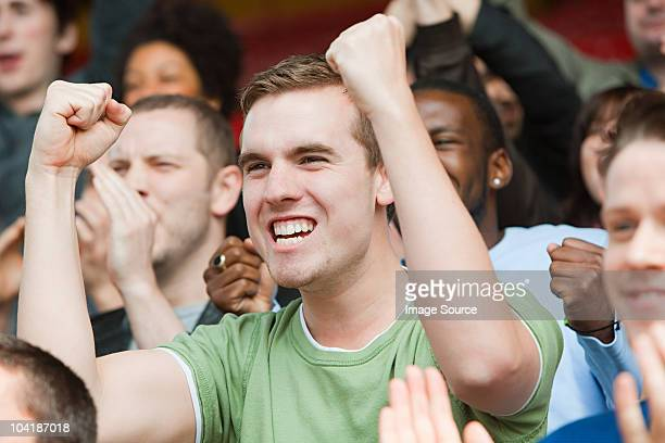 Man cheering at football match