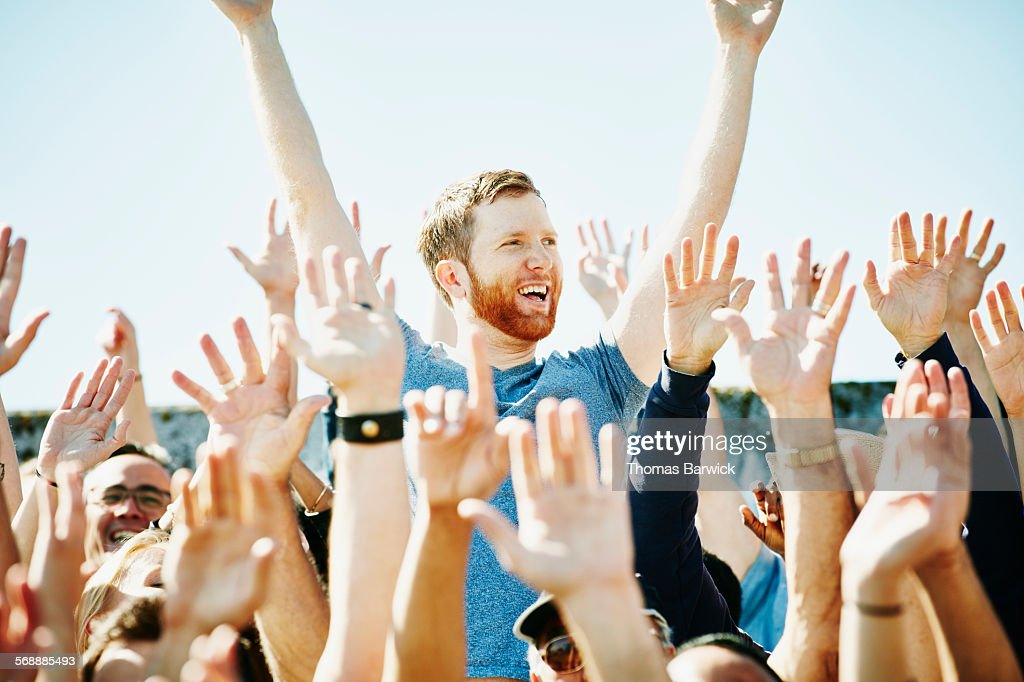 Man cheering in crowd with arms raised : Stock Photo