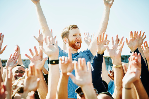 Man cheering in crowd with arms raised - gettyimageskorea