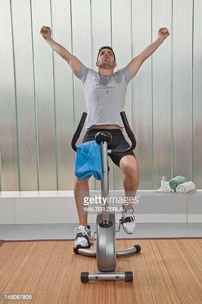 Man cheering on exercise machine