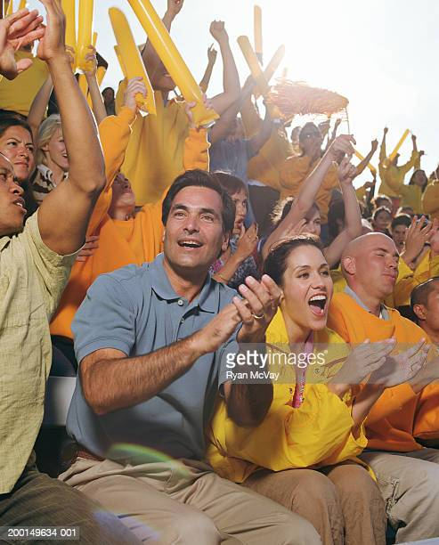 Man cheering with crowd in stadium