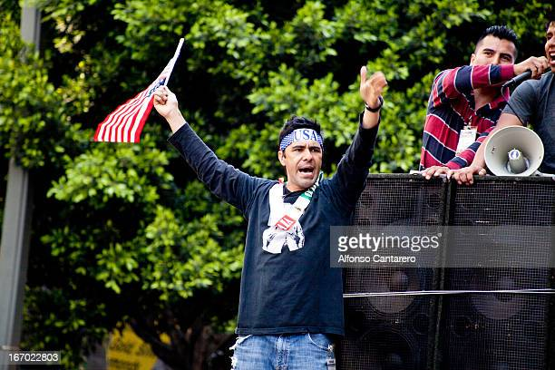 CONTENT] A man cheers and waves his US flag as he hears his fellow supporters speak of change Hundreds march in Downtown Los Angeles California in...