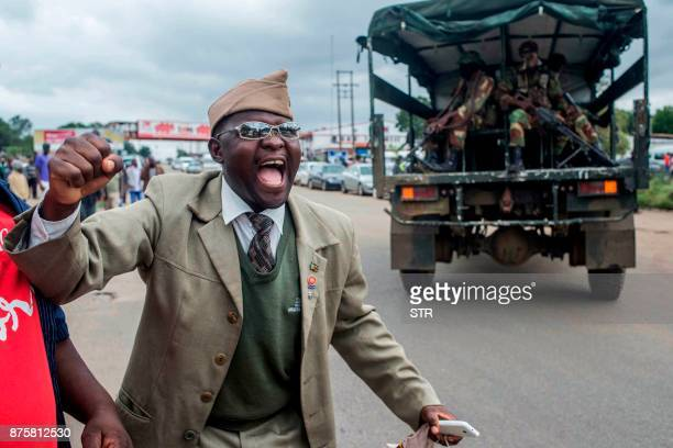 TOPSHOT A man cheers as a military vehicle loaded with soldiers drives past him during a rally to demand the resignation of Zimbabwe's president at...