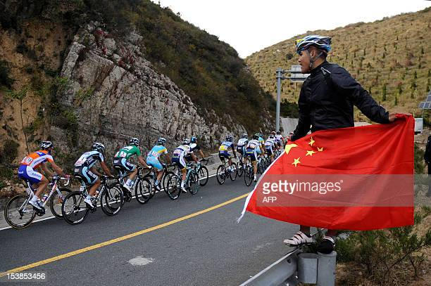 A man cheers with a national flag in his hands as cyclists ride past him during the second stage of the 2012 Tour of Beijing cycling race in Beijing...