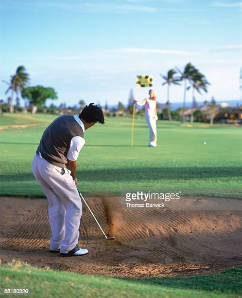 Man chipping out of sand trap