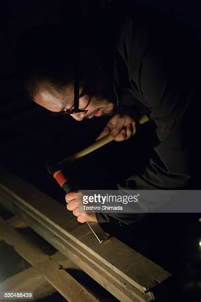 A man chiseling in the dark