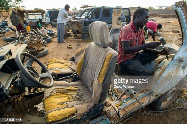 Man chisels apart a car at a yard where old vehicles are broken down for scrap, as Nigeriens struggle to cope with the challenges of daily life in...