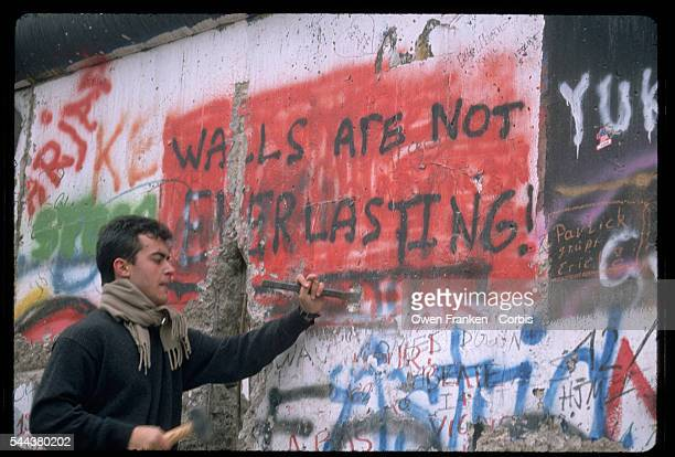 "Man chisels away at a graffiti covered section of the Berlin Wall which says ""Walls Are Not Everlasting!""after the fall of communism in Germany."