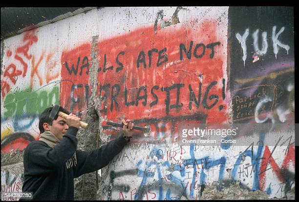 A man chisels away at a graffiti covered section of the Berlin Wall which says 'Walls Are Not Everlasting' after the fall of communism in Germany