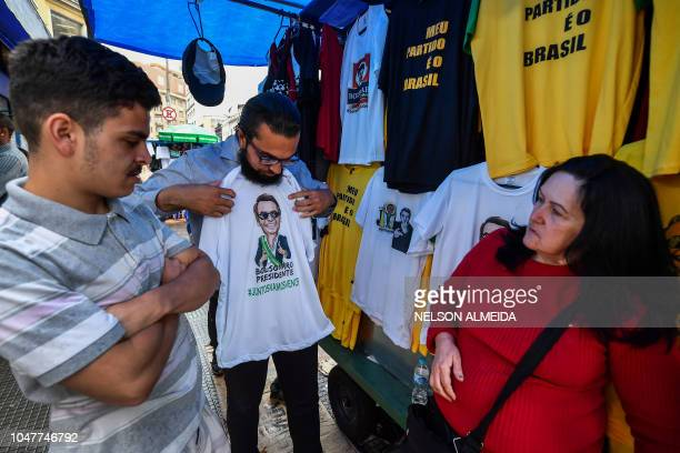 A man chooses a Tshirt with an image of presidential candidate for the Social Liberal Party Jair Bolsonaro in a popular shopping street in downtown...