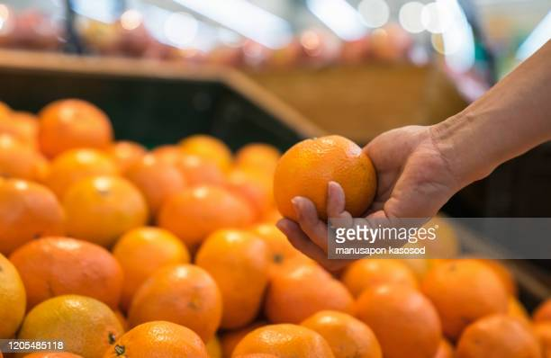 man chooses oranges in the supermarket. - tangerine stock pictures, royalty-free photos & images