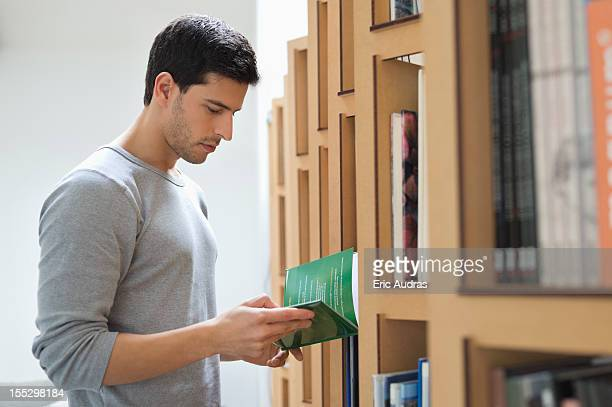 Man choosing a book from a bookshelf