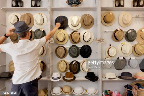 man choosing a hat in shop - hat stock pictures, royalty-free photos & images